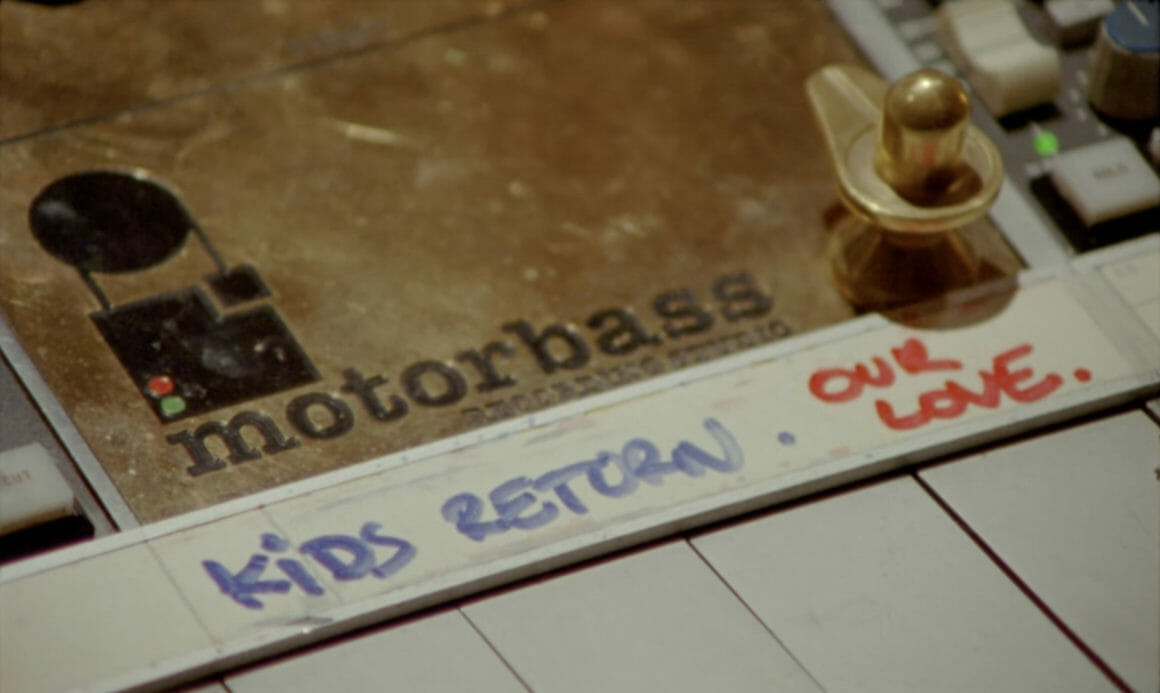 """Plan sur une table de mixage. Sous le logo motorbass gravé, sont écrits au feutre """"Kids Return"""" et """"our love""""."""