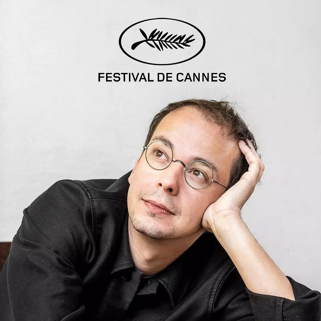 Portrait du musicien Rone, pose rêveuse la tête posée dans sa main. En fond, le logo du festival de Cannes.