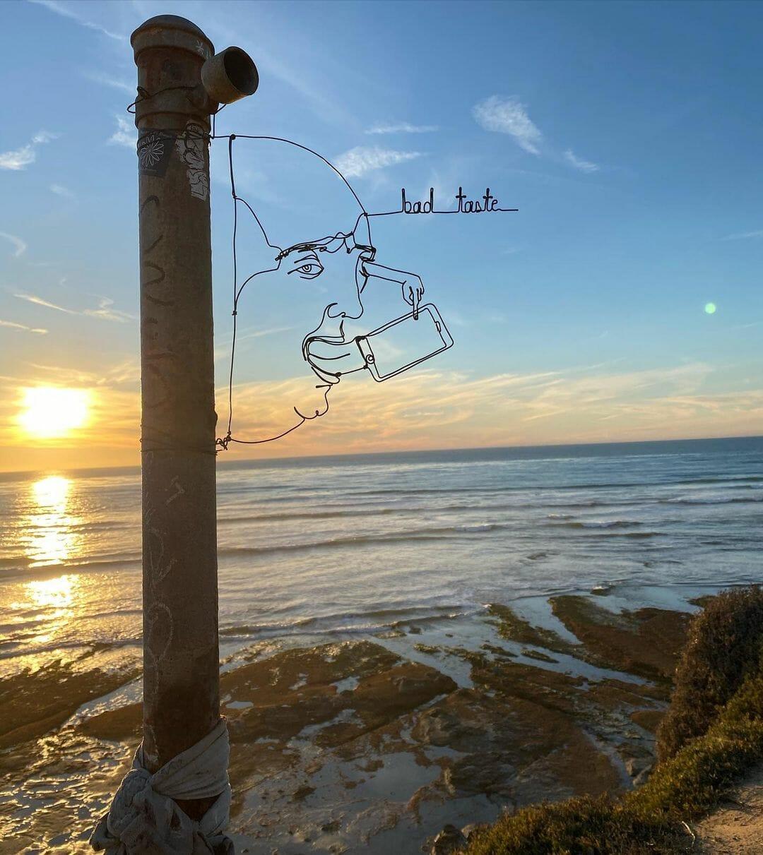 Sculpture en fil de fer abstraite d'un homme léchant un téléphone.