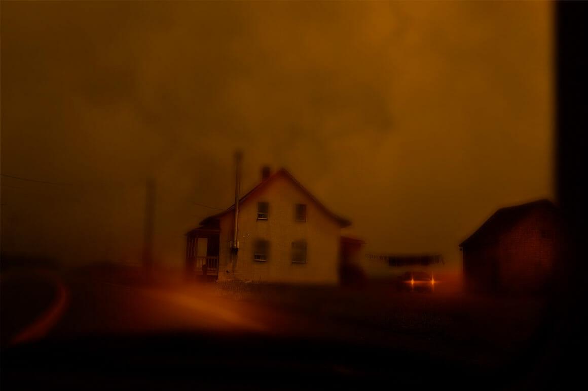 Photographie d'une maison isolée, l'atmosphère est floue et rouge.