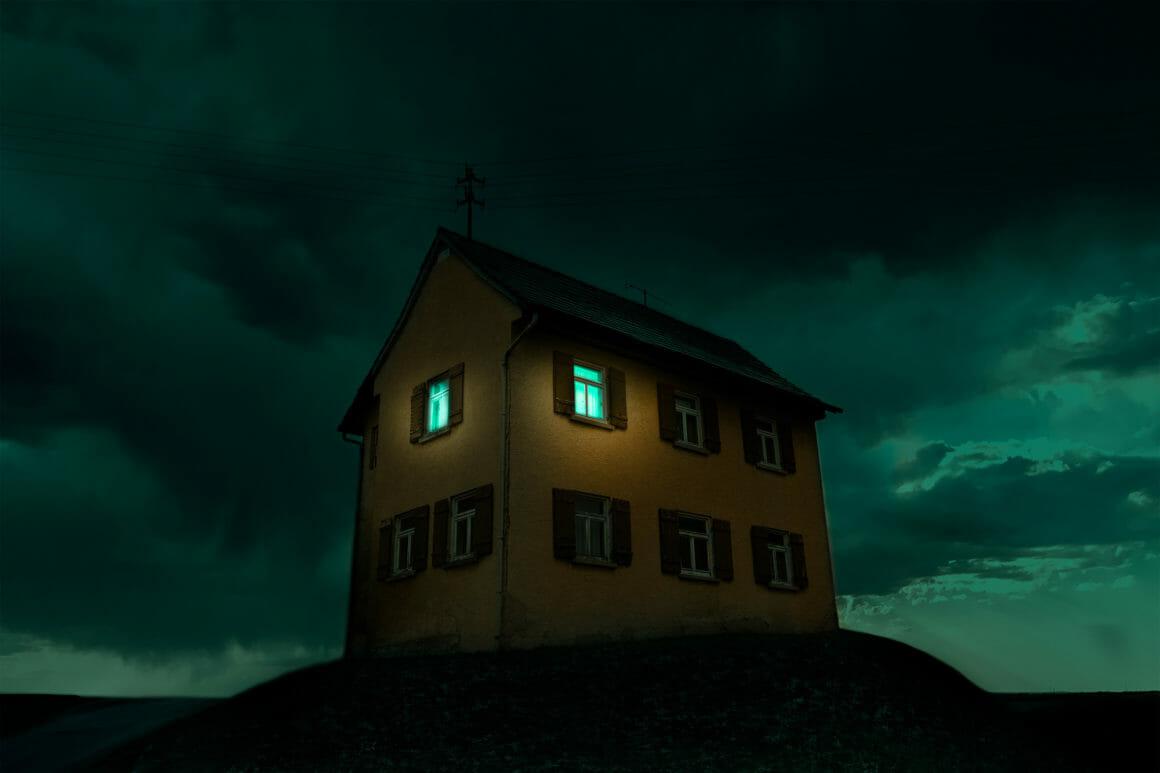 Photographie d'une maison sur une butte avec un ciel bleu.