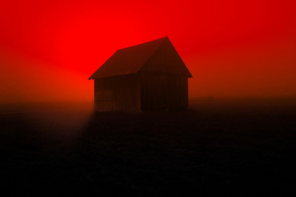Photographie d'une cabane en bois avec un ciel rouge.
