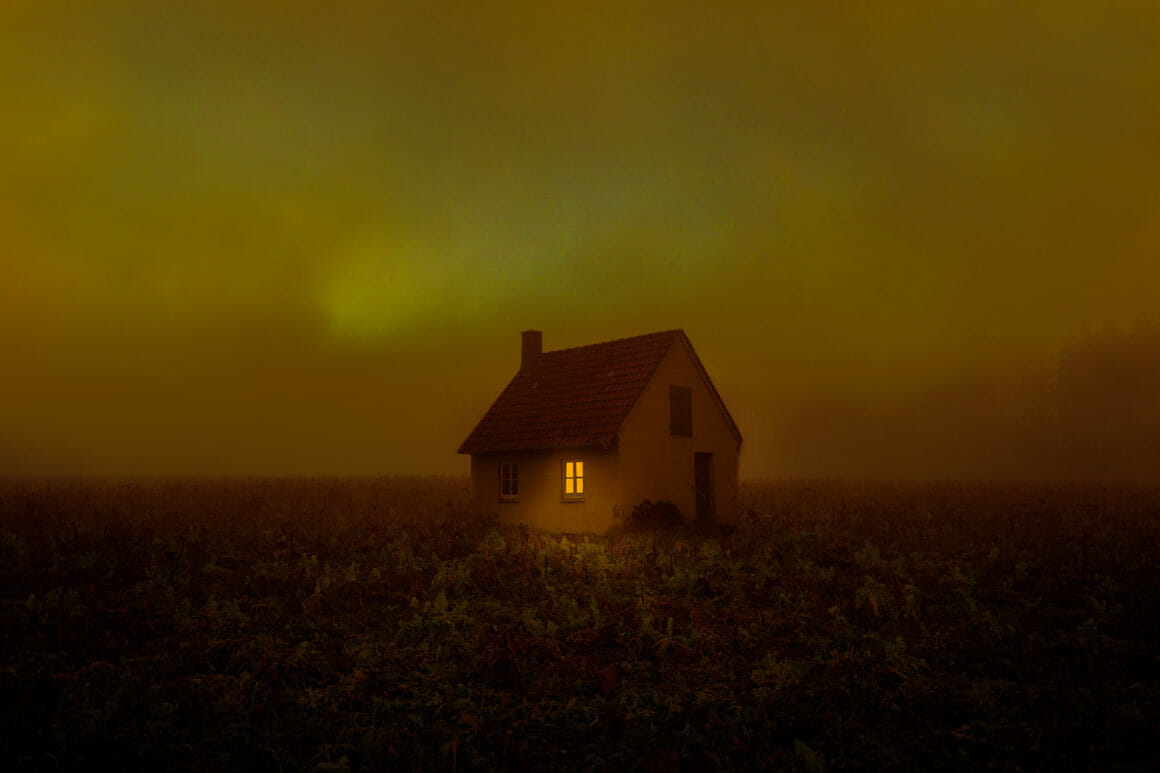 Photographie d'une maison isolée avec ciel lugubre.