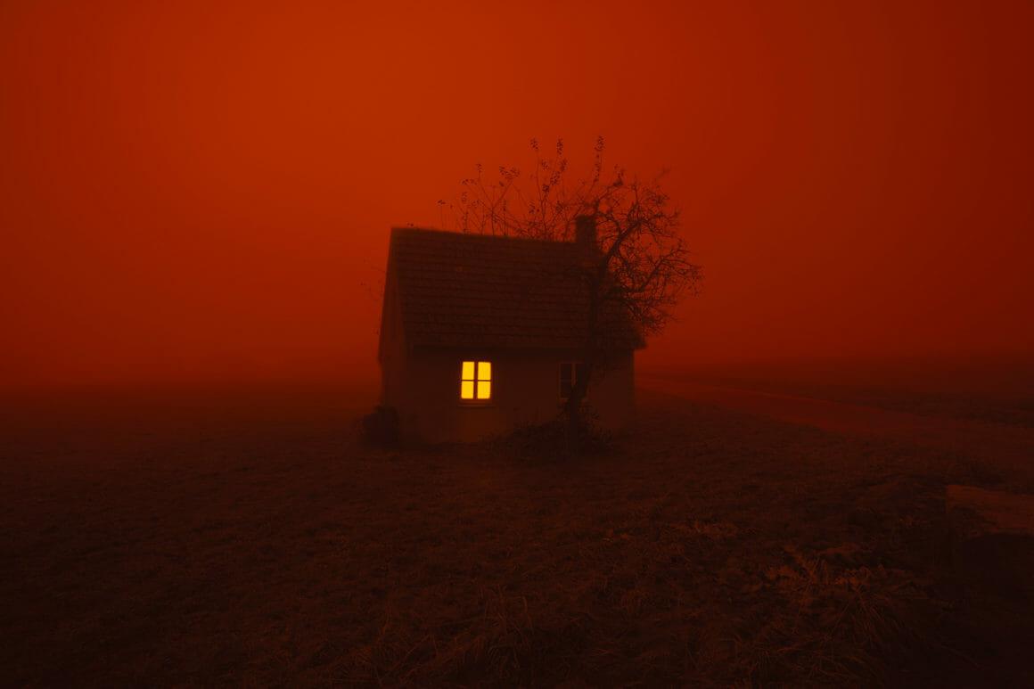 Photographie d'une maison isolée, le ciel est rouge.