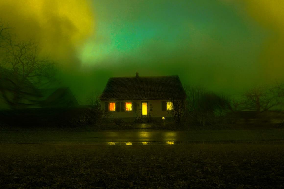 Photographie d'une maison isolée avec un ciel vert.