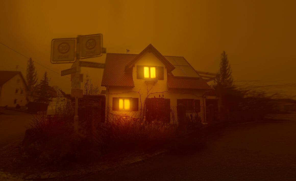 Photographie d'une vieille maison avec de la lumière jaune aux fenêtres.