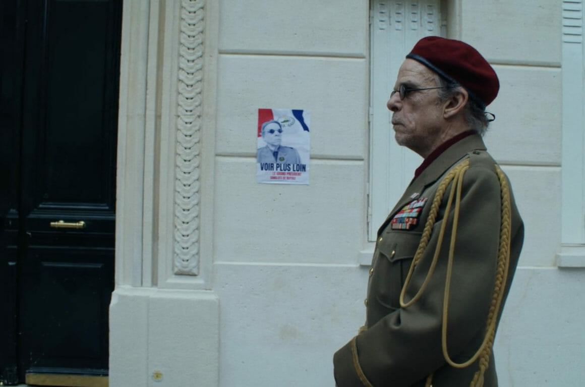 """De profil, un dictateur âgé se tient dans la rue. Derrière lui, une affiche à son image : """"Voir plus loin"""". Il porte sur le nez des lunettes, références aux """"lunettes spéciales"""" qui reviennent régulièrement dans """"écran total""""."""