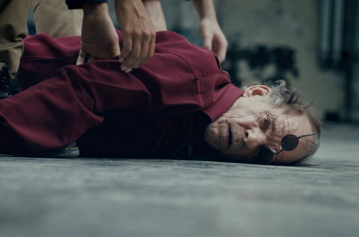 Posé au sol, le dictateur est mort, ses lunettes brisées sur le nez.