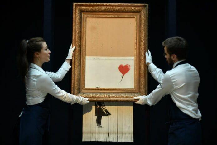 """Reproduction de l'oeuvre """"La petite fille au ballon"""" de Banksy broyée à moitié: une petite fille lâchant un ballon rouge en forme de coeur, ne laissant voir que le ballon sur fond blanc"""