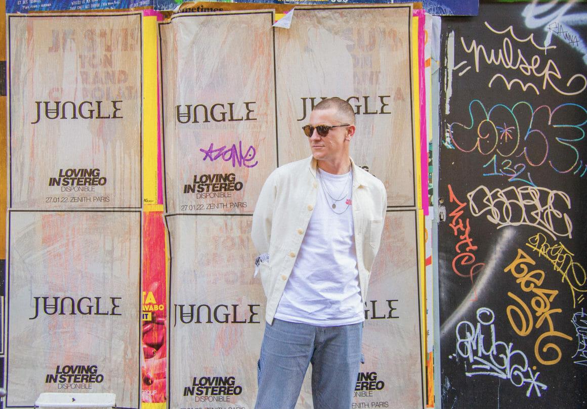Tom McFarland pose devant un mur où sont placardées des affiches du nouvel album de Jungle.
