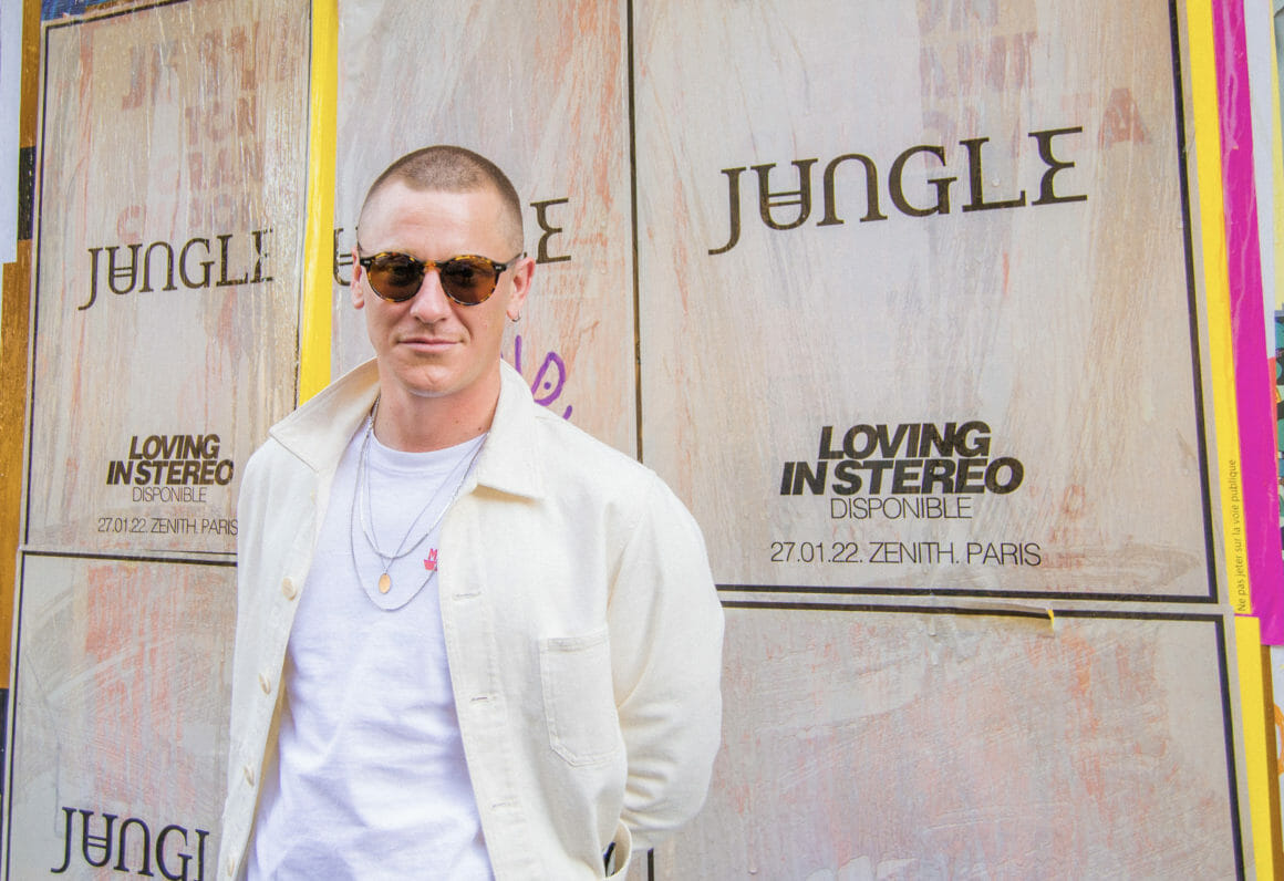 Tom McFarland pose devant un mur où sont placardées des affiches du nouvel album de Jungle (format portrait).