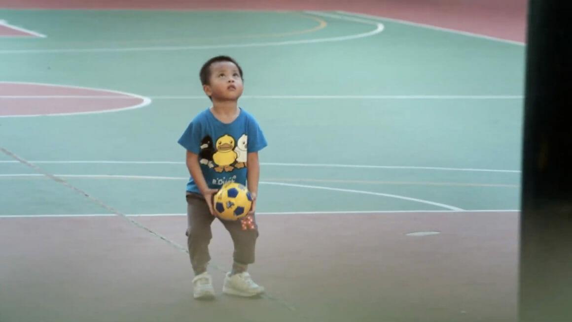 Un petit garçon asiatique lance un ballon sur un terrain de basket.