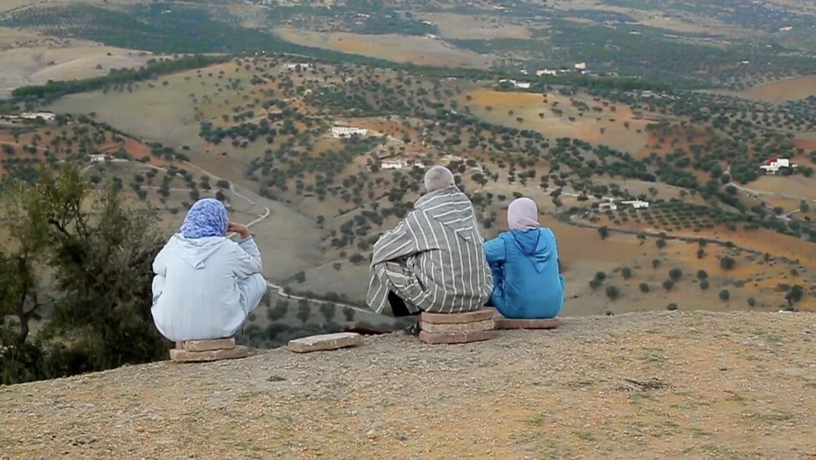 """Extrait de la vidéo """"La vie de tous les jours"""". Deux femme set un homme sont assis, de dos, à même le sol d'une colline surplombant un désert parsemé de points verts."""