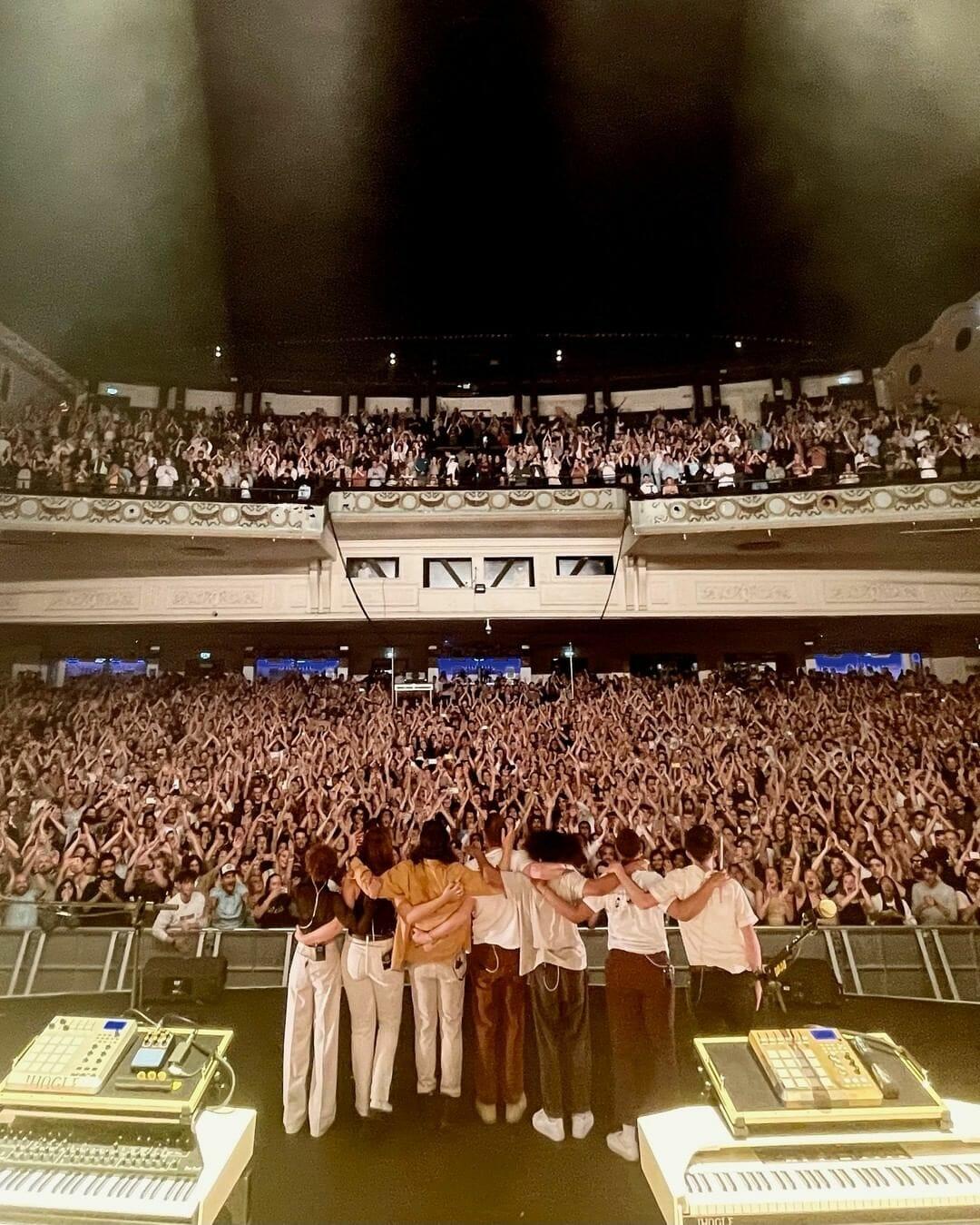 Le groupe se tient de dos, sur scène, face à une salle de concert pleine.