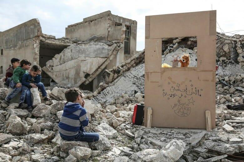 Des enfants sont assis dans les décombres d'un village en Syrie. Devant eux, un théâtre de marionnettes en carton.