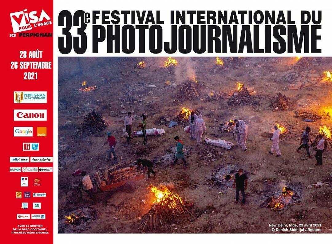 Affiche du 33e festival international du photojournalisme. Photographie de New Delhi, en avril dernier. Des corps sont incinérés de manière sommaire dans un champs, entourés de travailleurs maqués.