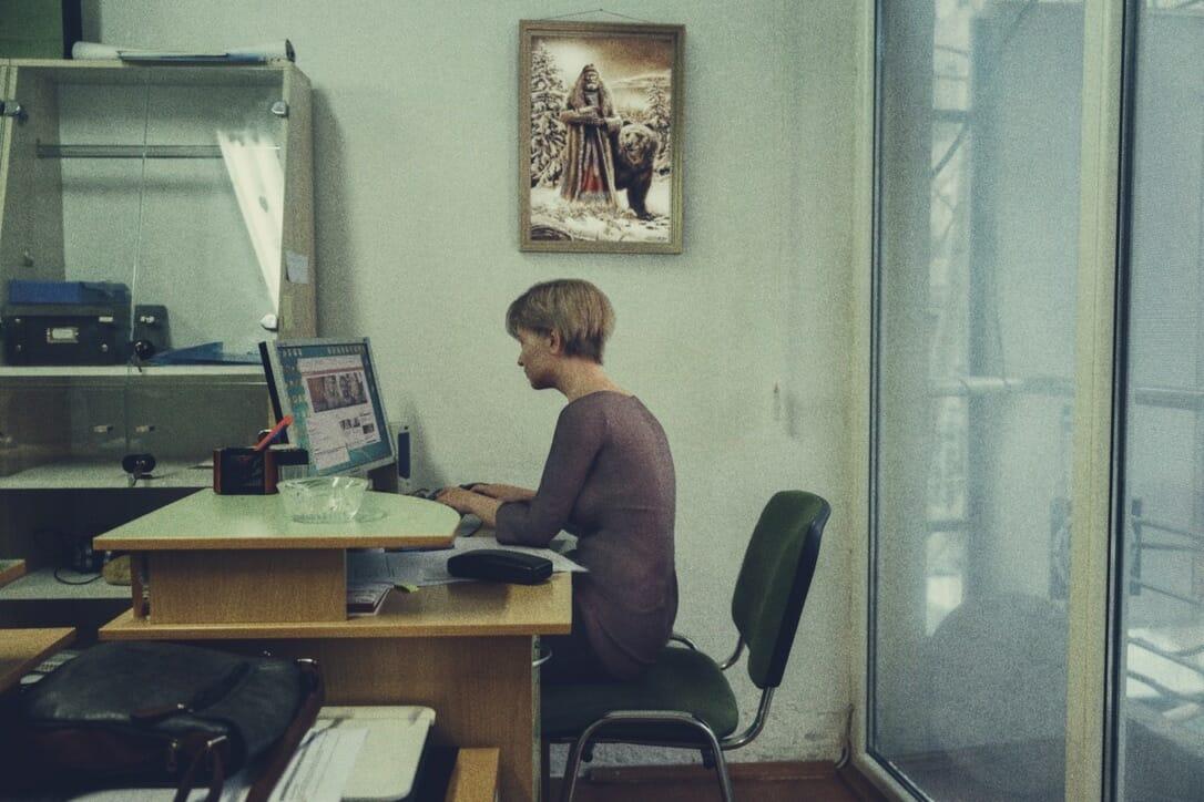 une femme est assise à un bureau sur son ordinateur