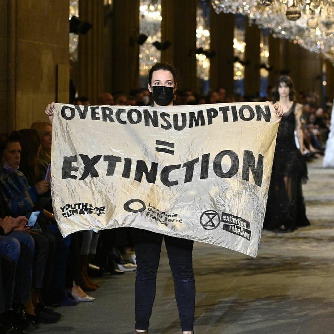 """une femme avec une pancarte """"surconsommation = extinction"""" dans un défilé"""