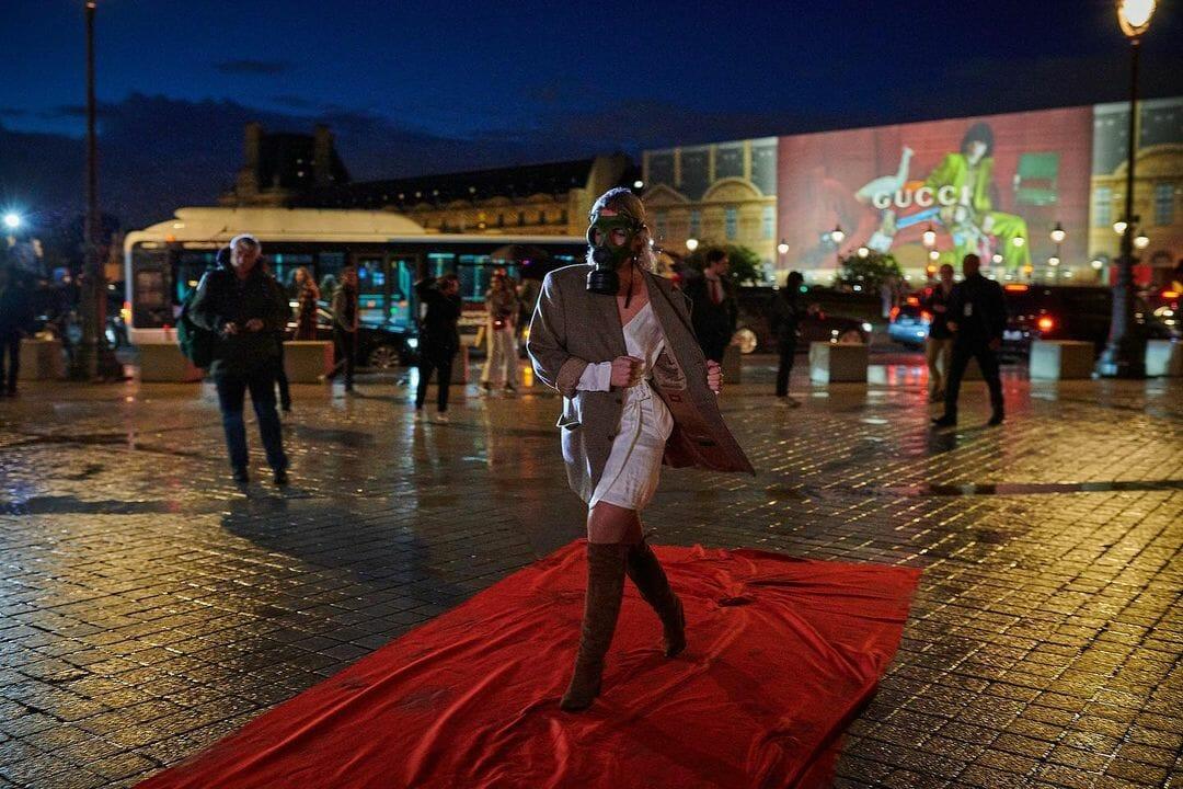 Un femme portant un masque à gaz sur un tapis rouge devant le louvre