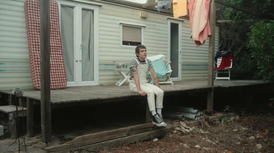extrait clip blond ou le chanteur se tient sur la terrasse d'un mobil-home