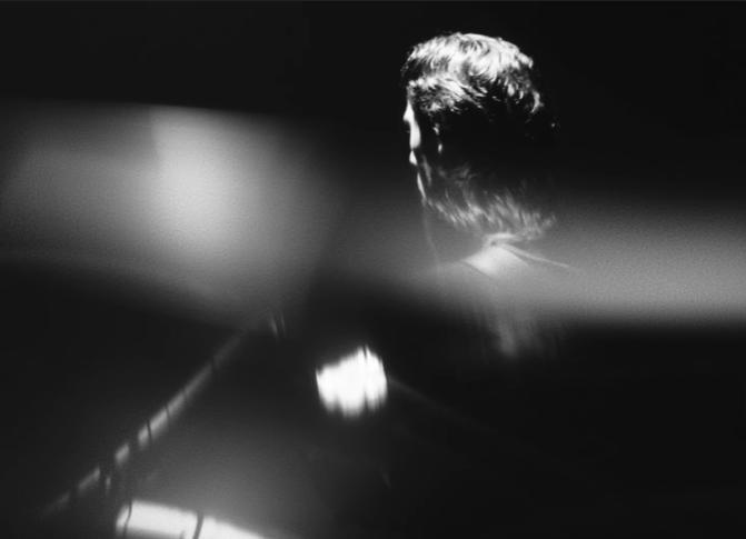 desmond myers dans son dernier clip musical Shadows. Noir et blanc, l'artiste tient une guitare