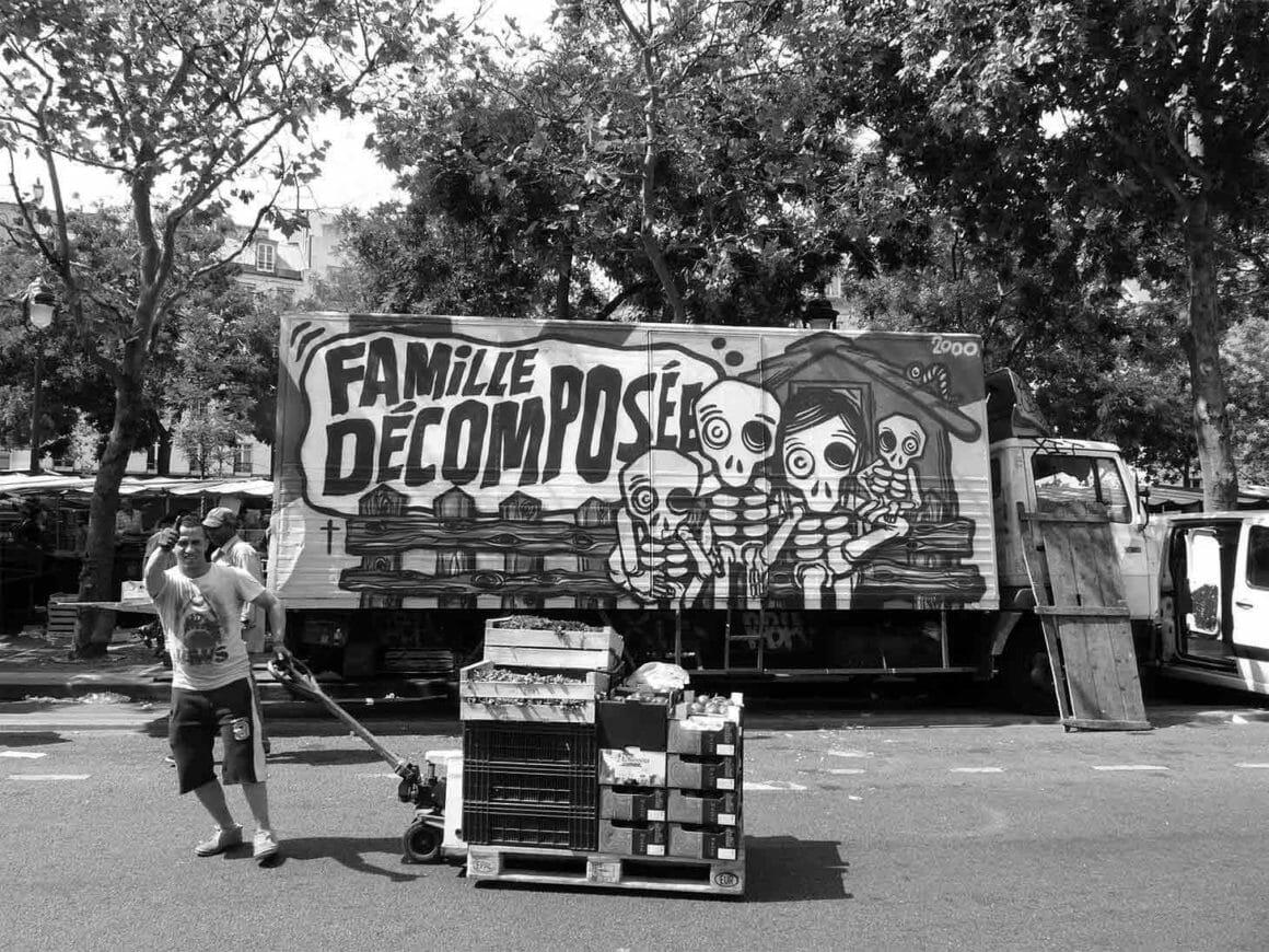 On voit un camion ornementé d'un graffiti du peintre Mygalo sur une place de marché