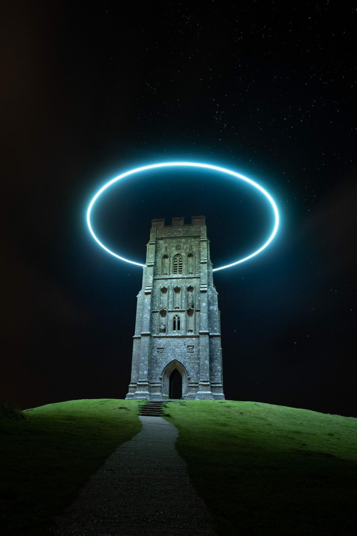 la tour de glastonbury photographié de nuit, entourée d'un halo lumineux qui l'éclaire